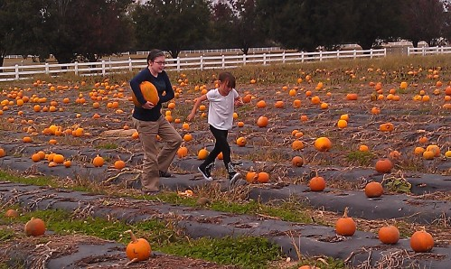 The daughter helping a little one carry a BIG pumpkin.