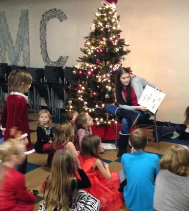 The Daughter reading Christmas books during gathering time for the AHG Christmas party